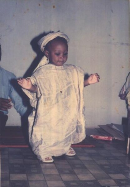 Jemila Abdulai as a baby in Nigeria, learning to walk in an African boubou. Father ready to support her if she falls.